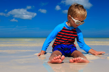 feet of little boy having fun on summer beach