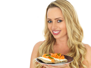 Young Woman Eating Smoked Salmon and Cream Cheese on a Cracker