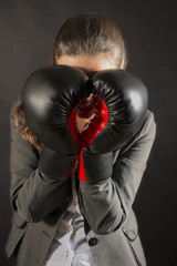Businesswoman covering her face with boxing gloves