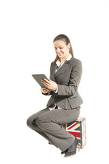 Businesswoman sitting on a vintage suitcase looking at tablet