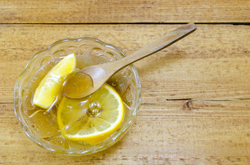 Glass plate filled with honey and lemon slices