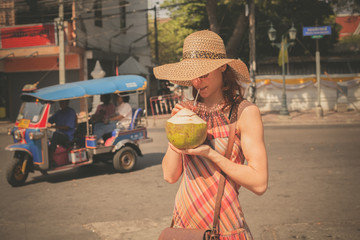 Woman drinking from coconut in the street
