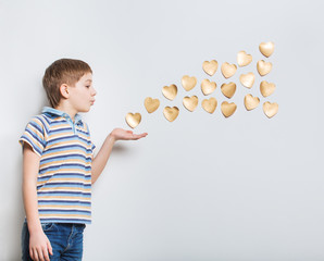 Boy blowing golden hearts from hand over light grey background