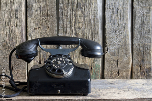 Old retro telephone on vintage boards - 76988490