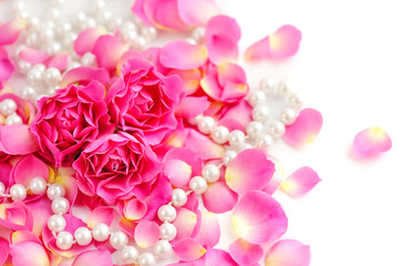 Pink roses and pearls on white background