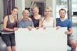 gemischte gruppe zeigt ein plakat im fitness-studio