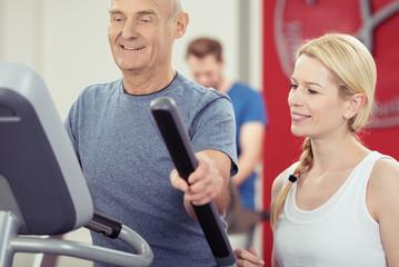 trainerin betreut einen älteren mann im fitness-club