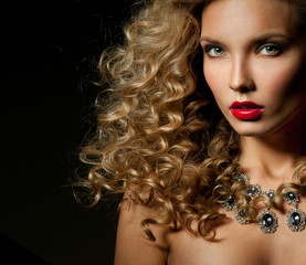 Beautiful woman with magnificent curly hair. Red lipstick. Neckl