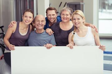 lachende gruppe zeigt ein leeres schild im fitness-studio