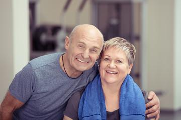 glückliches, älteres paar beim training im fitness-studio
