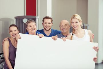 leute im fitness-studio zeigen ein weißes plakat