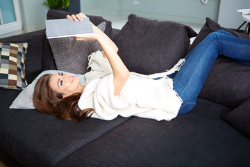 Cheerful woman lying on a cosy couch