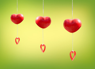 red heart mobile hanging on green background