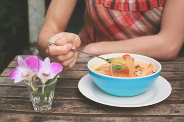 Woman eating tom yum soup