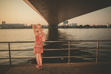 Young woman under bridge at sunset