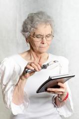 alte Frau schaut mit Lupe auf Taschenrechner