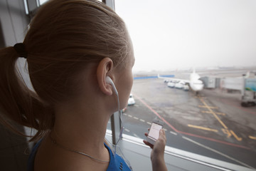 Woman in headphones looking at aiport area