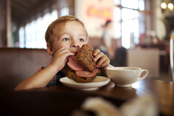 Little child having lunch with sandwich and tea in cafe