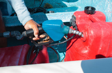 Man fueling tank of a motor boat before travel