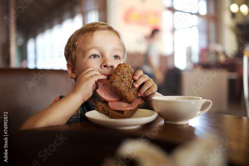 Leinwandbild Motiv Little child having lunch with sandwich and tea in cafe