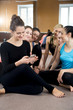 Group of happy sporty women using mobile phone on break in sport