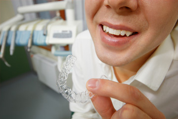 Smiling man holding silicone mouth guard
