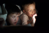 Fototapety Two boys watching movie or cartoon on pad at night