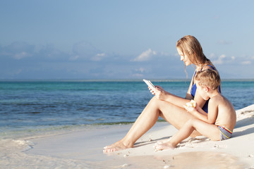 Mother and little son sitting by the sea with pad
