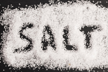 The word salt written into a pile of white granulated salt