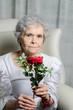 alte Frau riecht an Rose