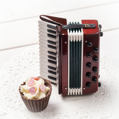 Chocolate candy and decorative accordion on a paper napkin