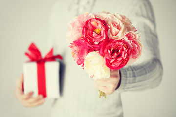 man holding bouquet of flowers and gift box