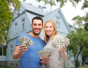 smiling couple showing money over house background