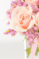 Peach roses and statice in a glass vase