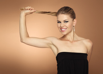 Happy smiling woman holding her long tail. Healthy hair ends