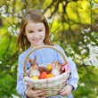 Adorable girl holding a basket of Easter eggs