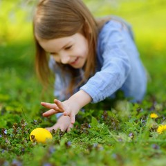 Adorable little girl hunting for an egg on Easter