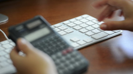 Person calculating tax on calculator and entering expenses