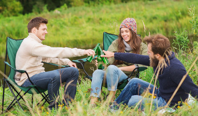 group of smiling tourists drinking beer in camping