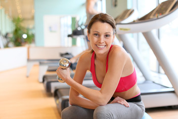 Athletic girl in gym center sitting on fitness ball