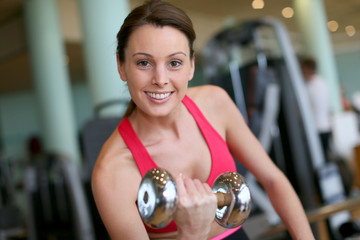 Cheerful athletic woman lifting dumbbells in gym