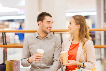 happy couple with shopping bags drinking coffee