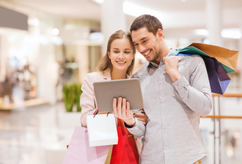 couple with tablet pc and shopping bags in mall
