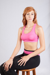 Redhead woman in exercise outfit, sitting relaxed