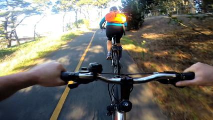POV bike riding woodland couple exercising lifestyle activity, USA