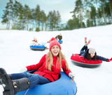 group of happy friends sliding down on snow tubes