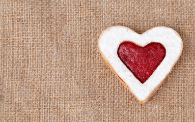 Heart shaped cookie for valentine's day on textile background wi