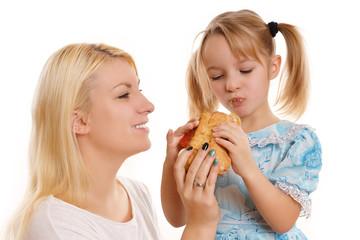 Mutter und Tochter teilen sich ein Brötchen