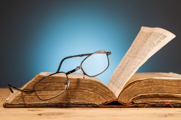 book   and  glasses on wooden table