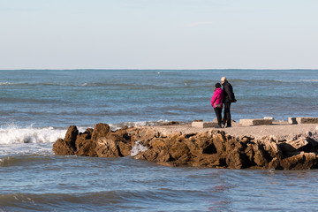 elderly couple enjoy the view on seacoast in winter